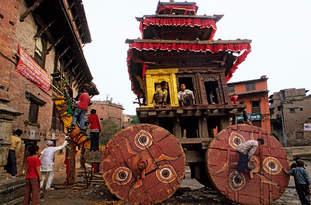 [NEPAL.KATHMANDUVALLEY 27477] 'Children on Bhairava's chariot.'  Bhaktapur's New Year's festival (Bisket) starts with a tug-of-war in Taumadhi Square, in which residents of the upper and lower halves of the city try to pull a chariot containing a mask of the god Bhairava to their respective sides. Its four solid-wooden wheels are regarded as sacred representations of the Veda's, ancient Hindu holy books. After the contest Bhaktapur's children play around in the vehicle. Photo Mick Palarczyk.