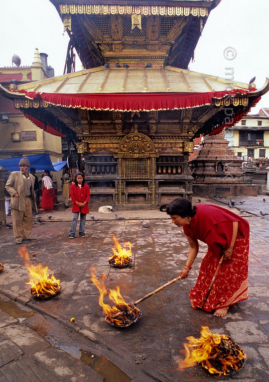 [NEPAL.KATHMANDUVALLEY 27219] 'Burnt-offering at Swayambhu.'  	At Swayambhu, west of Kathmandu, a woman is alighting a burnt-offering in front of the gilt-roofed Temple of Harati. This goddess, also known as Ajima, is revered as a protectress against childhood diseases. Photo Mick Palarczyk.