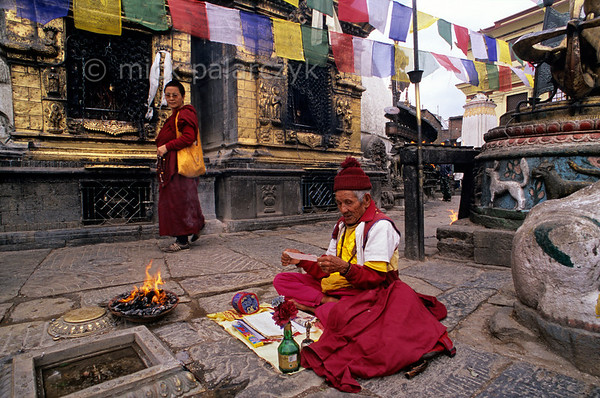 [NEPAL.KATHMANDUVALLEY 27225] 'Monk at Swayambhu.'  At the foot of Swayambhu stupa, west of Kathmandu, a Buddhist monk is reciting prayers near a burnt-offering. The two gold gilded shrines visible in the background are incorporated into the base of the stupa. The one on the right is dedicated to Akshobhya; facing the east it represents the cosmic element of conscousness. The shrine on the left is dedicated  to Vairochana, the master of the temple. Photo Mick Palarczyk.