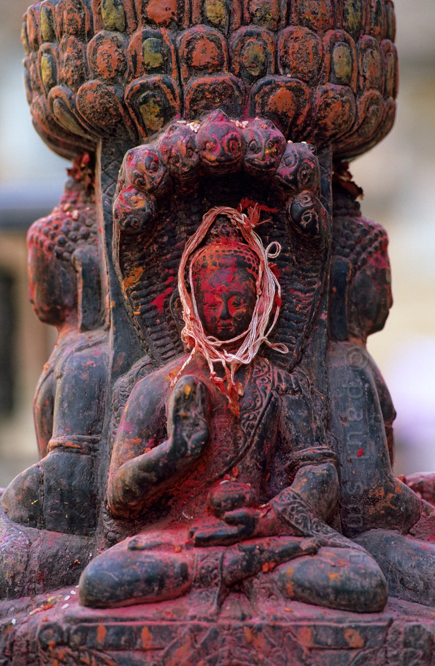 [NEPAL.KATHMANDUVALLEY 27527] 'Buddha in Thimi.'  In this statue at Thimi, Buddha, protected by an umbrella of holy snakes, has his head wrapped with holy threads. Photo Paul Smit.