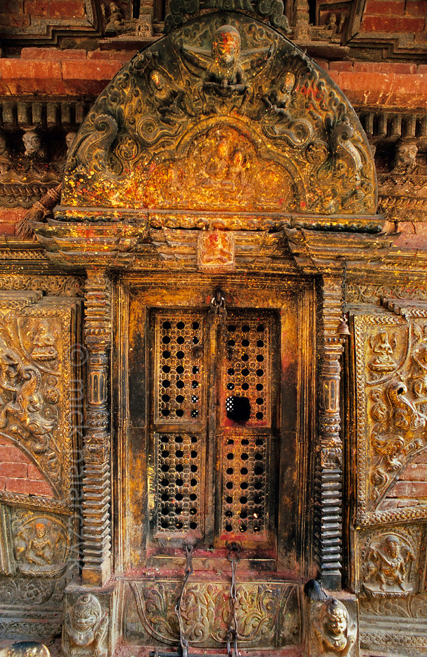 [NEPAL.KATHMANDUVALLEY 27562] 'Shrine door at Changu Narayan.'  Door of the Pashupatinath Shrine in the courtyard of Vishnu Temple at Changu Narayan. Red and yellow powder has been smeared on the torana  (wooden carving above a door) during puja offerings. Photo Mick Palarczyk.