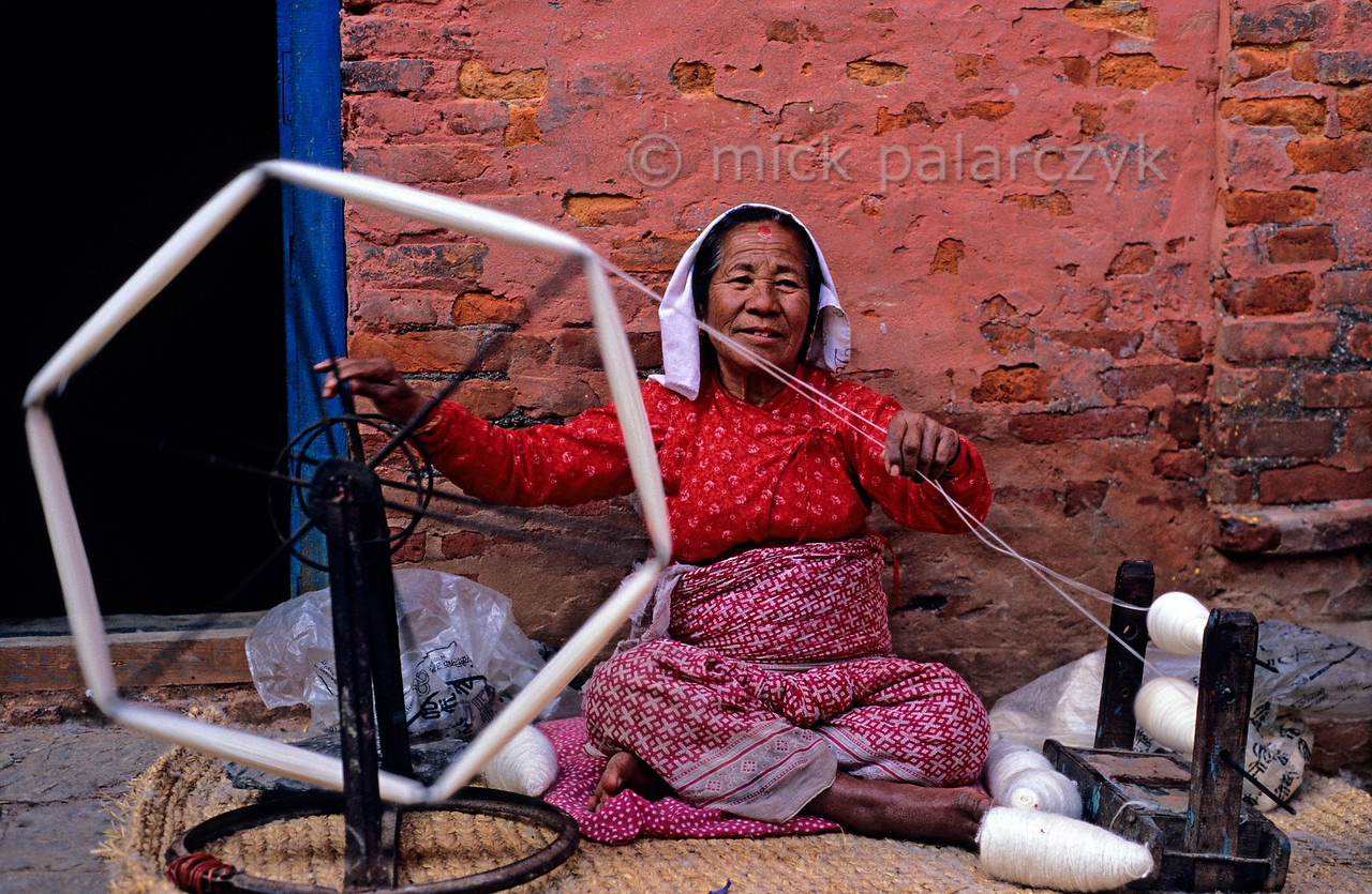 [NEPAL.KATHMANDUVALLEY 27368] 'Twining wool in Harisiddhi.'  In Harisiddhi, south of Patan, many women can be seen twining and spinning wool for Patan's carpet industry. Photo Mick Palarczyk.