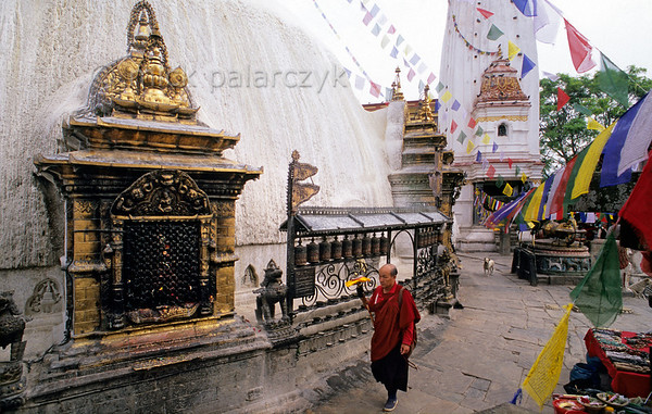 [NEPAL.KATHMANDUVALLEY 27220] 'Pilgrim at Swayambhu.'  	Twirling his hand-held prayer wheel, a Buddhist pilgrim makes a circumambulation of the central stupa at Swayambhu, west of Kathmandu. The gold gilded shrine incorporated in the base of the stupa (on the left) is dedicated to one of Buddha's consorts. Photo Mick Palarczyk.