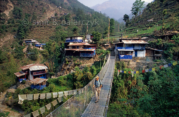 [NEPAL 27020] 'Tirkhedhungga village.'  	In the Annapurna Conservation Area a footbridge crosses the Tirkhedhungga Khola towards some teahouses of the Tirkhedhungga village. Such teahouses can be found anywhere along the trekking routes in the Annapurna region and provide food and simple accommodation for the trekkers. Photo Mick Palarczyk & Paul Smit.