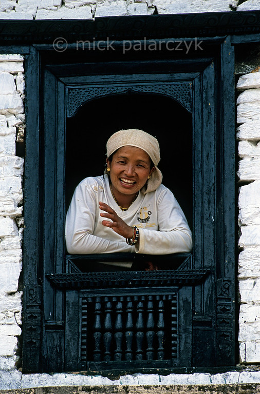 [NEPAL 27165] 'Innkeeper in Ghandrung.'  Innkeeper Anju Gurung leans out of the window of her Family Cottage teahouse in Ghandrung (Annapurna Conservation Area). Photo Mick Palarczyk.