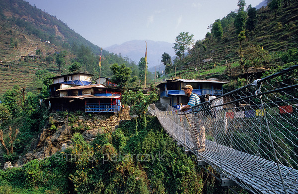 [NEPAL 27018] 'Tirkhedhungga village.'  	In the Annapurna Conservation Area a footbridge crosses the Tirkhedhungga Khola towards some teahouses of the Tirkhedhungga village. Such teahouses can be found anywhere along the trekking routes in the Annapurna region and provide food and simple accommodation for the trekkers. Photo Mick Palarczyk & Paul Smit.