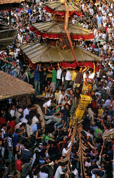 [NEPAL.KATHMANDUVALLEY 27462] 'Bisket festival in Bhaktapur's Taumadhi Square.'  Bhaktapur's New Year's festival (Bisket) starts with a tug-of-war in Taumadhi Square, in which residents of the upper and lower halves of the city try to pull a chariot to their respective sides. The enormous temple shaped rath (vehicle of the gods) contains a mask of the god Bhairava. Photo Paul Smit.