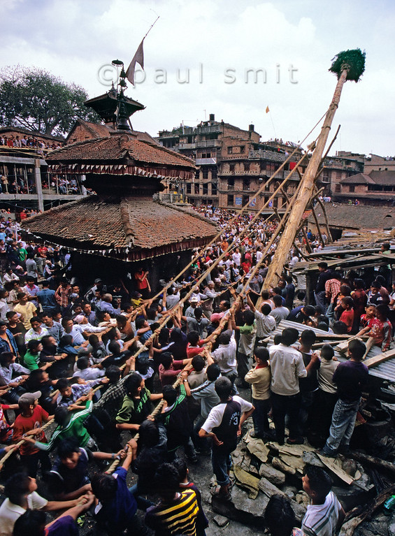 [NEPAL.KATHMANDUVALLEY 27505] 'Erecting a New Year's pole in Bhaktapur.'  	On Bhaktapur's Potter's Square, during the New Year's festival (Bisket), men of the pottery-making caste try to erect a huge lingam pole. The pole is a phallic emblem representing the power of Shiva and Bhairava as well as a symbol of the New Year, thought to bring protection and prosperity to the people of Bhaktapur. Photo Paul Smit.