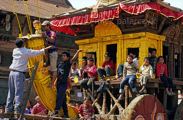 [NEPAL.KATHMANDUVALLEY 27473] 'Preparations for Bhaktapur's Bisket festival.'  Bhaktapur's New Year's festival (Bisket) starts with a tug-of-war in Taumadhi Square, in which residents of the upper and lower halves of the city try to pull a chariot containing a mask of the god Bhairava to their respective sides. In preparation for the contest, the metal figure of Betal (Bhairava's mythological bearer) is attached to the heavy upward-curving beam extending to the front of the vehicle. After Bisket Betal will be returned to his temple where he will be bound face-downwards to a beam, as he is considered an evil spirit who brings ill fortune. Photo Mick Palarczyk.