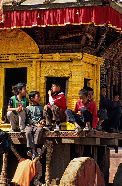 [NEPAL.KATHMANDUVALLEY 27474] 'Children on Bhairava's chariot.'  Bhaktapur's New Year's festival (Bisket) starts with a tug-of-war in Taumadhi Square, in which residents of the upper and lower halves of the city try to pull a chariot containing a mask of the god Bhairava to their respective sides. During the preparations of the contest Bhaktapur's children play around in the vehicle. Photo Mick Palarczyk.