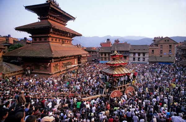 [NEPAL.KATHMANDUVALLEY 27448] 'Tug-of war in Bhaktapur.'  Bhaktapur's New Year's festival (Bisket) starts with a tug-of-war in Taumadhi Square, in which residents of the upper and lower halves of the city try to pull a chariot to their respective sides. The enormous temple shaped rath (vehicle of the gods) contains a mask of the god Bhairava, which is normally kept in the Bhairava Temple that is visible on the left. Photo Mick Palarczyk.
