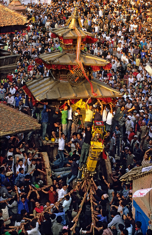 [NEPAL.KATHMANDUVALLEY 27456] 'Bisket festival in Bhaktapur's Taumadhi Square.'  	Bhaktapur's New Year's festival (Bisket) starts with a tug-of-war in Taumadhi Square, in which residents of the upper and lower halves of the city try to pull a chariot to their respective sides. The enormous temple shaped rath (vehicle of the gods) contains a mask of the god Bhairava. Photo Paul Smit.