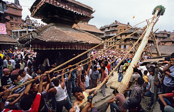[NEPAL.KATHMANDUVALLEY 27499] 'Erecting a New Year's pole in Bhaktapur.'  	On Bhaktapur's Potter's Square, during the New Year's festival (Bisket), men of the pottery-making caste try to erect a huge lingam pole. The pole is a phallic emblem representing the power of Shiva and Bhairava as well as a symbol of the New Year, thought to bring protection and prosperity to the people of Bhaktapur. Photo Paul Smit.