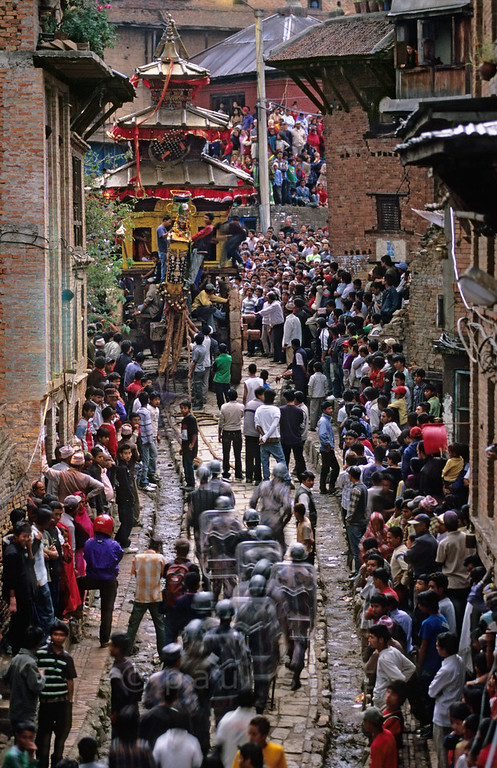 [NEPAL.KATHMANDUVALLEY 27479] 'Vehicle of the gods in Bhaktapur.'  	During Bhaktapur's New Year's festival (Bisket) the enormous temple shaped rath (vehicle of the gods) containing a mask of the god Bhairava is tugged from Taumadhi Square through this narrow street in the direction of Chuping Ghat. Photo Paul Smit.