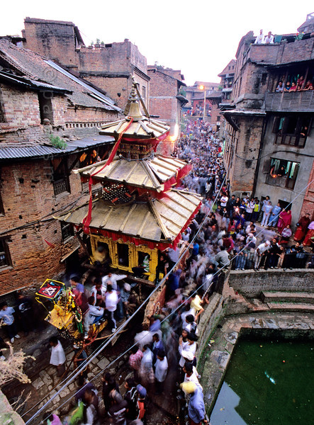 [NEPAL.KATHMANDUVALLEY 27481] 'Vehicle of the gods in Bhaktapur.'  During Bhaktapur's New Year's festival (Bisket) the enormous temple shaped rath (vehicle of the gods) containing a mask of the god Bhairava is tugged from Taumadhi Square through this narrow street in the direction of Chuping Ghat. Photo Paul Smit.