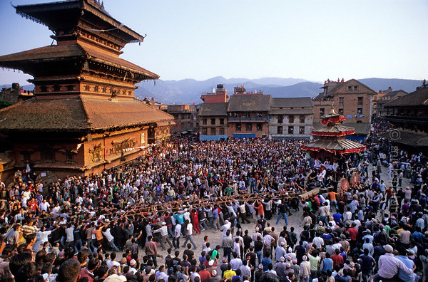 [NEPAL.KATHMANDUVALLEY 27449] 'Tug-of war in Bhaktapur.'  Bhaktapur's New Year's festival (Bisket) starts with a tug-of-war in Taumadhi Square, in which residents of the upper and lower halves of the city try to pull a chariot to their respective sides. The enormous temple shaped rath (vehicle of the gods) contains a mask of the god Bhairava, which is normally kept in the Bhairava Temple that is visible on the left. Photo Mick Palarczyk.
