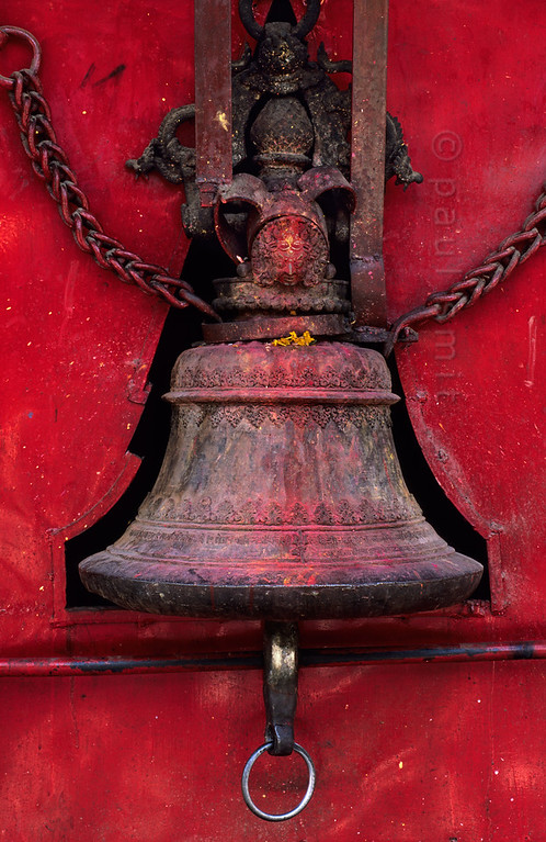 [NEPAL.KATHMANDUVALLEY 27282] 'Bell at Kathmandu's shrine of Pachali Bhairava.'  The top of a bell at Kathmandu's shrine of Pachali Bhairava is decorated with the head of Bhairava.  Bhairava is the fierce manifestation of Shiva, associated with annihilation and the march of time. He can be identified here by his bulging eyes, his mustache and the crescent moon of Shiva on his forehead. Photo Paul Smit.