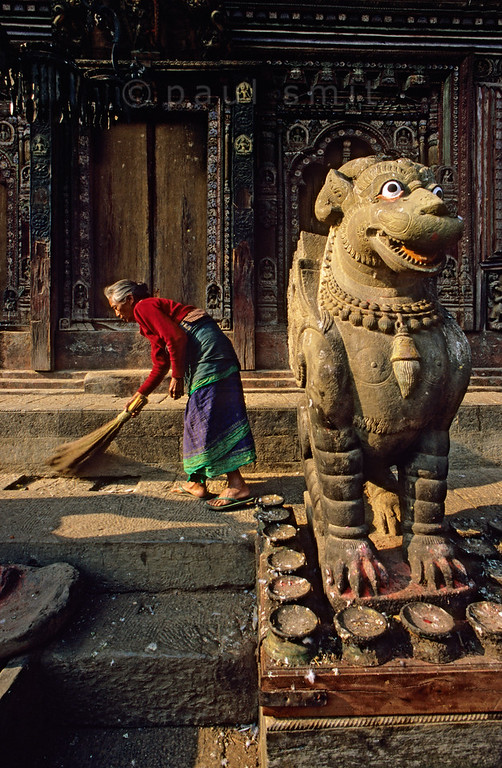 [NEPAL.KATHMANDUVALLEY 27533] 'Mythical monster at Changu Narayan.'  The northern entrance of the Vishnu Temple (ca. 1700) at Changu Narayan (north of Bhaktapur) is guarded by a mythical monster while its plinth is kept clean by a local old woman. Photo Paul Smit.