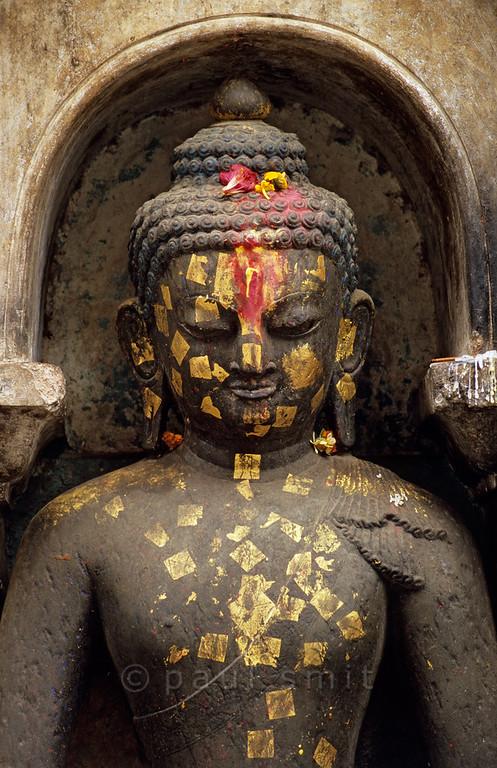[NEPAL.KATHMANDUVALLEY 27231] 'Buddha at Swayambhu.'  At Swayambhu stupa, west of Kathmandu, worshippers have glued gold-leaves to a statue of Buddha as an offering. Photo Paul Smit.