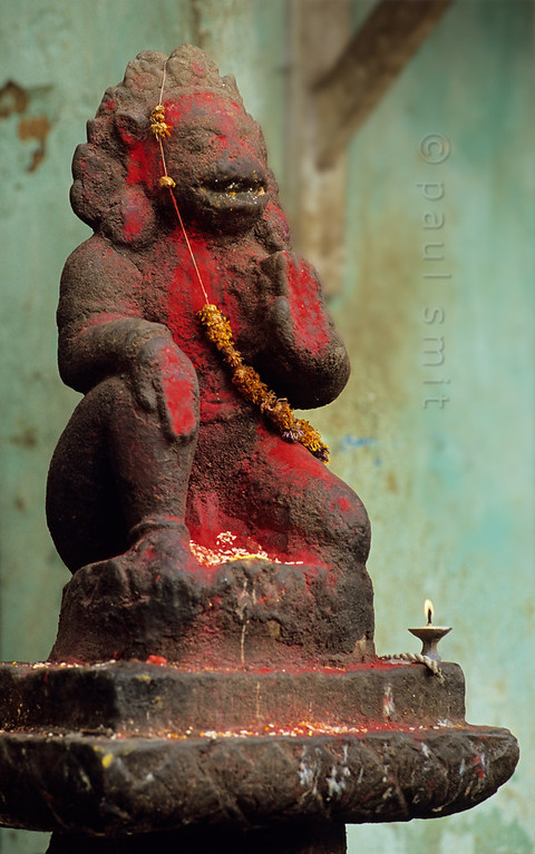 [NEPAL.KATHMANDUVALLEY 27235] 'Hanuman at Swayambhu stupa.'  Statue of Hanuman on the temple grounds of Swayambhu stupa, at the western outskirts of Kathmandu has received a puja offering of rice and a flower garland. Owing to his ability to ward of evil spirits, the Hindu monkey god Hanuman is one of the most popular gods in Nepal. His statues are often covered in vermilion paste. Photo Paul Smit.