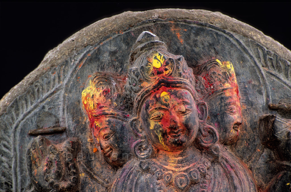 [NEPAL.KATHMANDUVALLEY 27359] 'Relief in Kirtipur.'  A relief with a three-headed goddess can be found on the grounds of the Chilandeo Stupa in Kirtipur, southwest of Kathmandu. Yellow and red powder has been smeared on the sculpture during puja offerings. Photo Paul Smit.
