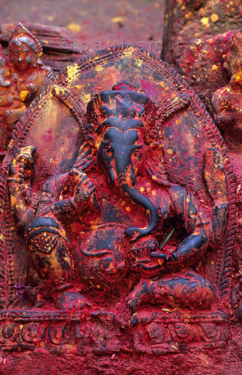 [NEPAL.KATHMANDUVALLEY 27582] 'Ganesh at Naubise.'  A small hilltop shrine at Naubise in the valley of the Mahesh Khola, just west of the Kathmandu Valley, holds a metalwork relief of Ganesh covered in red powder. Photo Paul Smit.