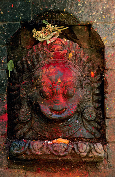 [NEPAL.KATHMANDUVALLEY 27387] 'Bhairava in Bhaktapur.'  	Sculpture of Bhairava in Bhaktapur. Bhairava is the fierce manifestation of Shiva, associated with annihilation and the march of time. He can be identified here by his bulging eyes and the crescent moon of Shiva in his hair. The sculpture has received offerings of flowers and red powder. Photo Paul Smit.