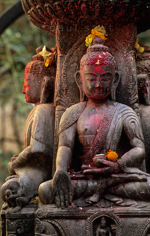 [NEPAL.KATHMANDUVALLEY 27347] 'Buddhas in Patan.'  A statue with four buddhas facing the directions of the compass occupies a small square south of Patan's Durbar Square. During puja offerings the sculpture has received donations of coloured powder and flowers. Photo Paul Smit.