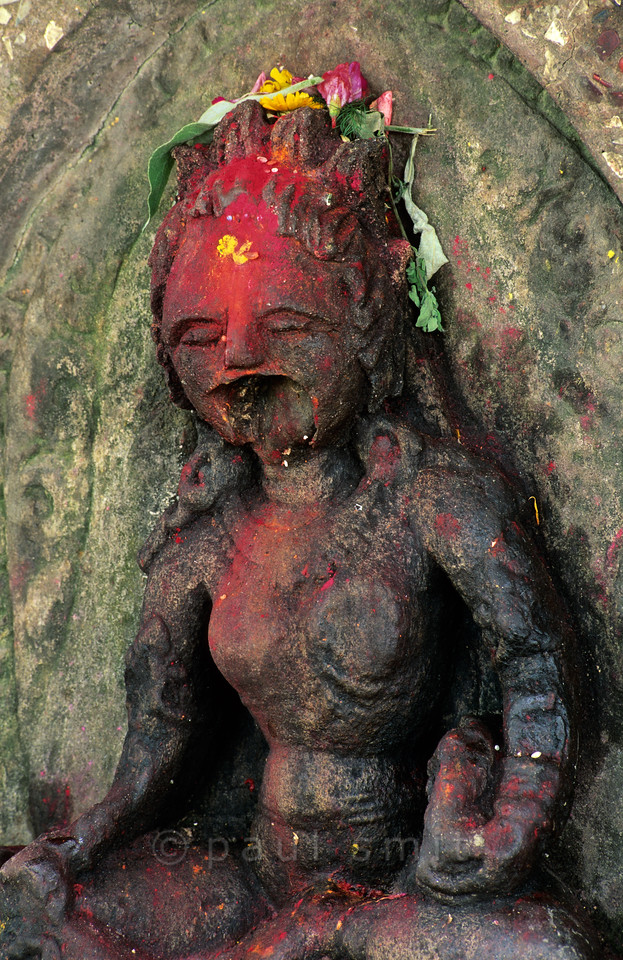 [NEPAL.KATHMANDUVALLEY 27421] 'Screaming goddess in Bhaktapur.'  This statue of Kali, Hindu Goddess of Destruction, on Bhaktapur's Hanuman Ghat (along the Hanumante River) has lost its lower jaw, giving the deity a particular freightening appearance. The goddess has received offerings of flowers and red powder. Photo Paul Smit.