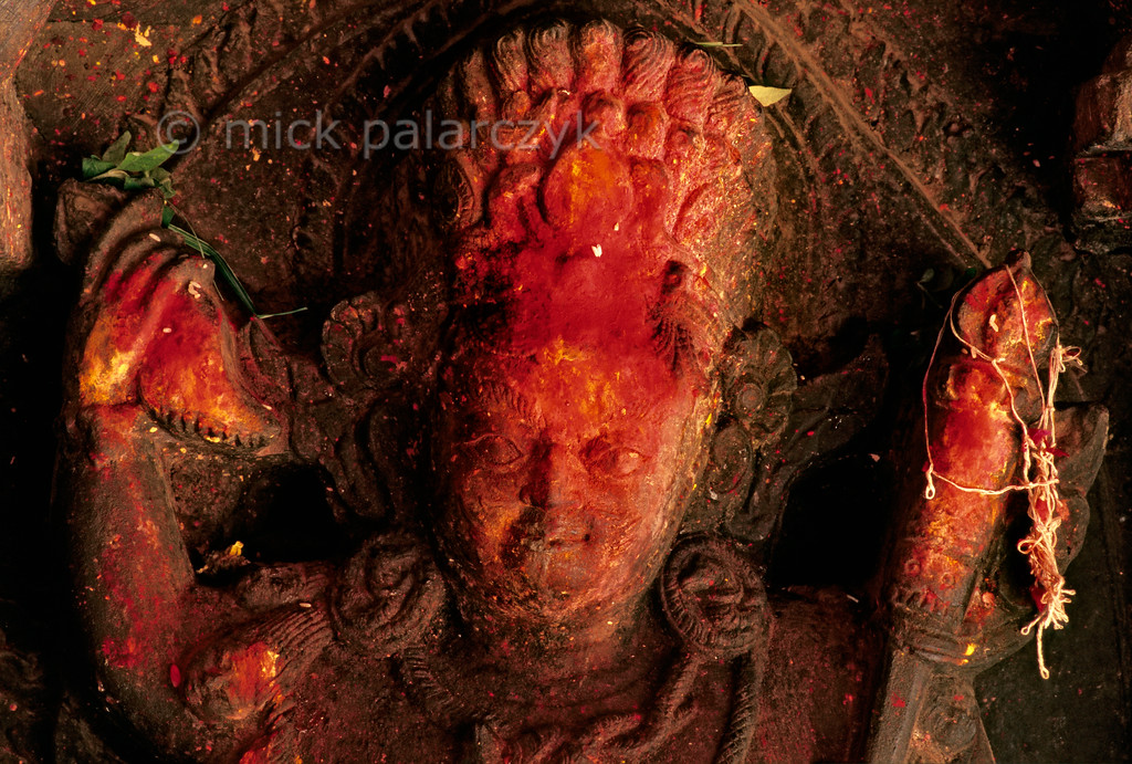 [NEPAL.KATHMANDUVALLEY 27335] 'Head of Bhairava.'  Statue of the Hindu God Bhairava in Patan's former Yampi monastery. Bhairava is the fierce manifestation of Shiva, associated with annihilation and the march of time. Here he is wearing earrings of twisted snakes and his fierceness seem to be further augmented by the red powder worshippers have smeared on his head. Photo Mick Palarczyk.