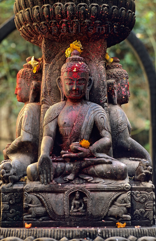 [NEPAL.KATHMANDUVALLEY 27345] 'Buddhas in Patan.'  	A statue with four buddhas facing the directions of the compass occupies a small square south of Patan's Durbar Square. During puja offerings the sculpture has received donations of coloured powder and flowers. Photo Paul Smit.