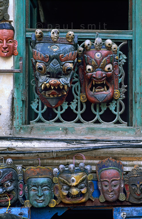 [NEPAL.KATHMANDUVALLEY 27270] 'Mask shop at Kathmandu's Durbar Square.'  	The window of a mask shop at Kathmandu's Durbar Square is decorated with masks of Bhairava. The fierce looking Bhairava, god of annihilation and the march of time, is a popular subject for masks. He is thought to preside over cremation grounds, hence the garland of skulls around his head. Photo Paul Smit.