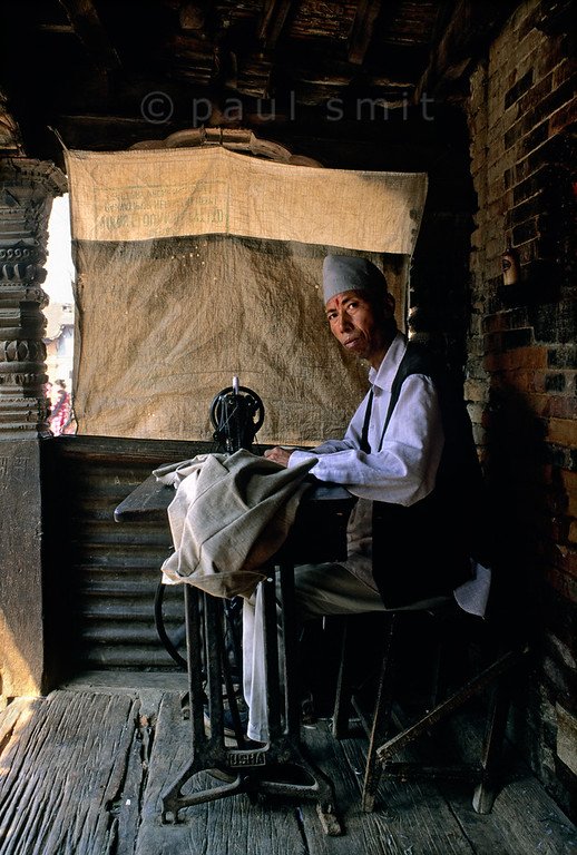 [NEPAL.KATHMANDUVALLEY 27390] 'Tailor in Bhaktapur.'  	A tailor is working in front of his house in Bhaktapur. Photo Paul Smit.