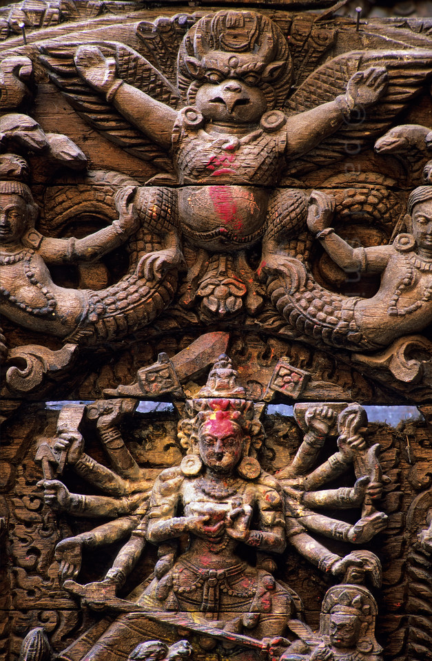 """[NEPAL.KATHMANDUVALLEY 27264] 'Torana of Kumari Chowk in Kathmandu.'  Wood-carved torana in the Kumari Chowk, the residence of the city's """"living goddess"""". The house of the Kumari is situated on the south side of Kathmandu's Durbar Square.  On this torana (wooden carving above a door) Garuda (half man - half bird) is shown clasping a pair of Nagas(snakes). The many armed goddess Taleju Bhawani, the personal deity of Nepal's Malla dynasty, is shown below the figure of Garuda.. Photo Paul Smit."""