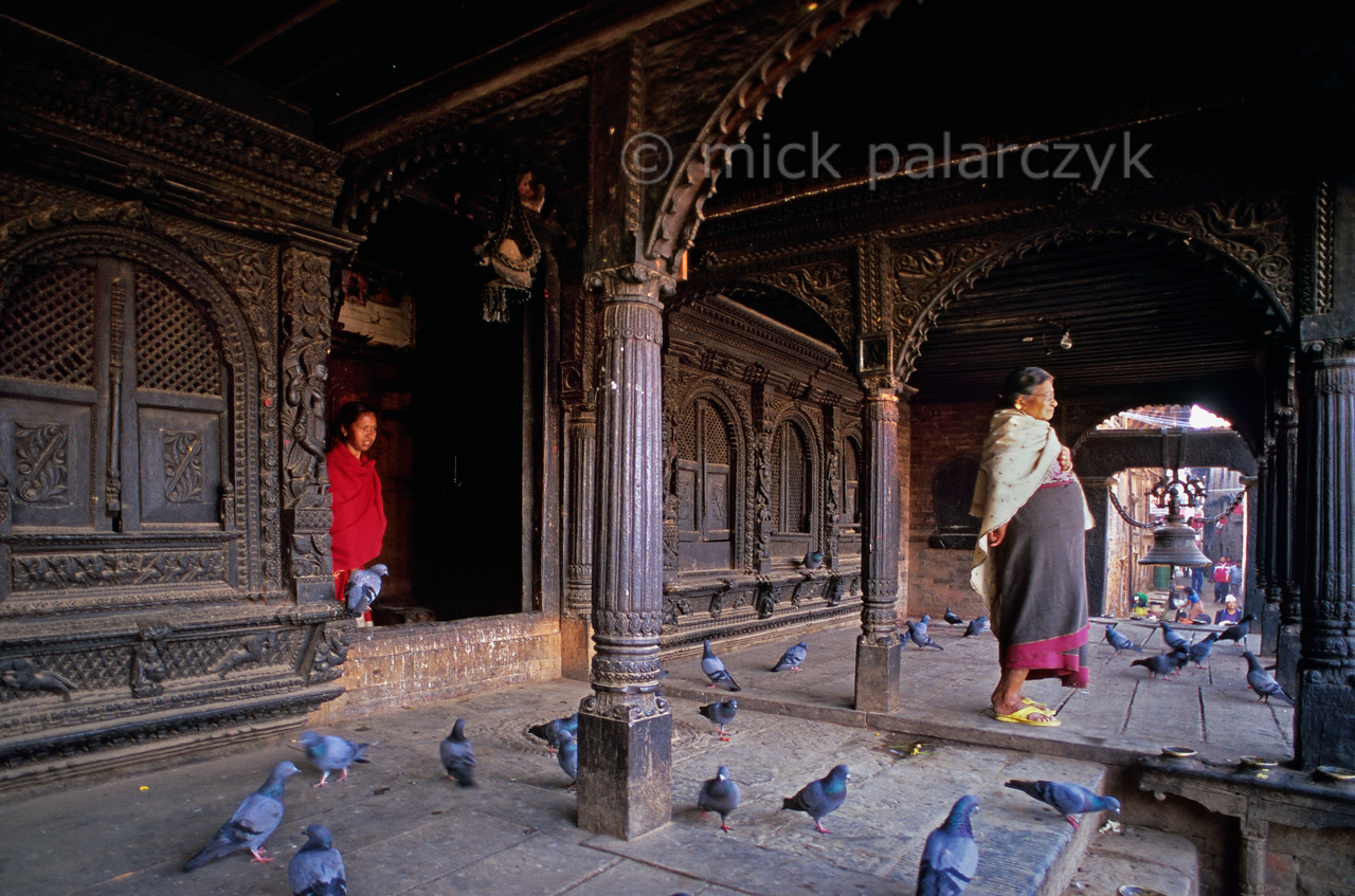 [NEPAL.KATHMANDUVALLEY 27408] 'Dattatraya Temple.'  From the pigeon crowded gallery of the Dattatraya Temple two women stand gazing across Bhaktapur's Dattatraya Square, after having paid their respect to the temple's god. Photo Mick Palarczyk.