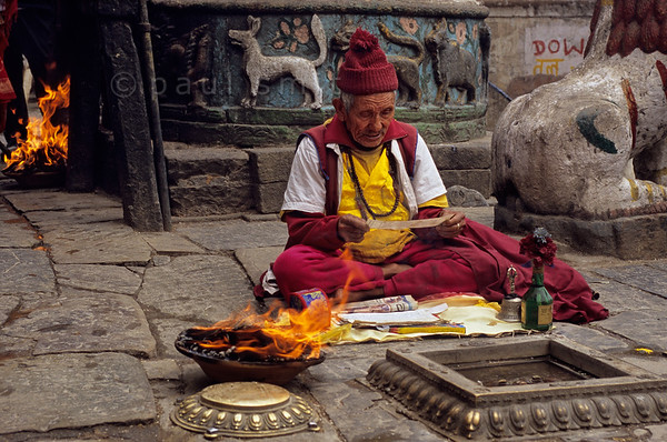 [NEPAL.KATHMANDUVALLEY 27227] 'Monk at Swayambhu.'  	At the foot of Swayambhu stupa, west of Kathmandu, a Buddhist monk is reciting prayers  near a burnt-offering. Photo Paul Smit.