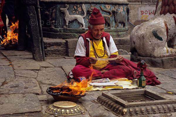 [NEPAL.KATHMANDUVALLEY 27227] 'Monk at Swayambhu.'  At the foot of Swayambhu stupa, west of Kathmandu, a Buddhist monk is reciting prayers  near a burnt-offering. Photo Paul Smit.