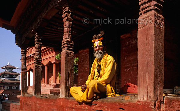[NEPAL.KATHMANDUVALLEY 27271] 'Sadhu on Kathmandu's Durbar Square.'  	A sadhu, or holy man, is basking in the morning sun on the west side of Kathmandu's Durbar Square. Photo Mick Palarczyk.