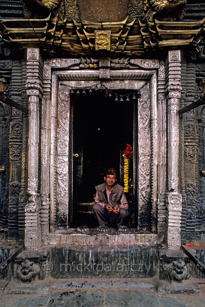 [NEPAL.KATHMANDUVALLEY 27336] 'Silver gate in Patan.'  The entrance of Patan's Rato Machhendranath Temple (1673) is decorated with silver repoussé. Rato Machhendranath is Patan's god of rain and plenty. To Buddhists he is the Tantric edition of Avalokiteshvara, while to Hindus he is a version of Shiva. His image is carted through the streets each year during city's most important festival. Photo Mick Palarczyk.