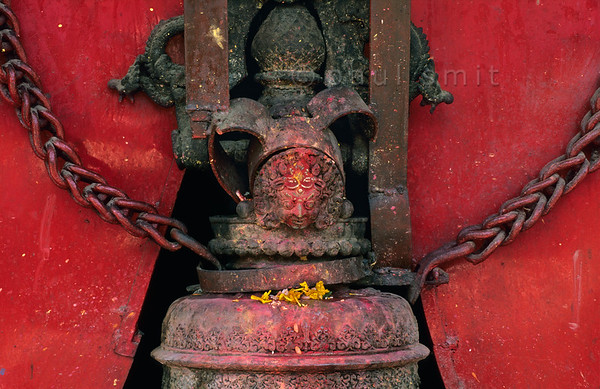 [NEPAL.KATHMANDUVALLEY 27284] 'Bell at Kathmandu's shrine of Pachali Bhairava.'  	The top of a bell at Kathmandu's shrine of Pachali Bhairava is decorated with the head of Bhairava.  Bhairava is the fierce manifestation of Shiva, associated with annihilation and the march of time. He can be identified here by his bulging eyes, his mustache and the crescent moon of Shiva on his forehead. Yellow flowers have been offered to the god during a puja offering. Photo Paul Smit.