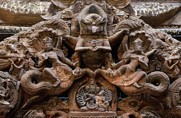 [NEPAL.KATHMANDUVALLEY 27321] 'Torana at the Sundari Chowk in Patan.'  	Wood-carved torana in the Sundari Chowk courtyard of Patan's Royal Palace.  On this torana (wooden carving above a door) Garuda (half man - half bird) is shown clasping a pair of Nagas(snakes). Below the figure of Garuda (who has lost his beak in thus sculpture)the many armed goddess Taleju Bhawani is shown. Photo Paul Smit.