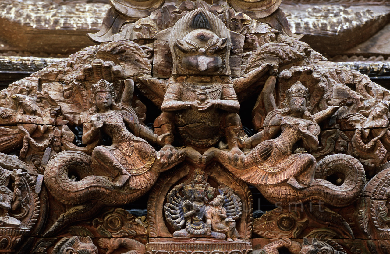 [NEPAL.KATHMANDUVALLEY 27321] 'Torana at the Sundari Chowk in Patan.'  Wood-carved torana in the Sundari Chowk courtyard of Patan's Royal Palace.  On this torana (wooden carving above a door) Garuda (half man - half bird) is shown clasping a pair of Nagas(snakes). Below the figure of Garuda (who has lost his beak in thus sculpture)the many armed goddess Taleju Bhawani is shown. Photo Paul Smit.