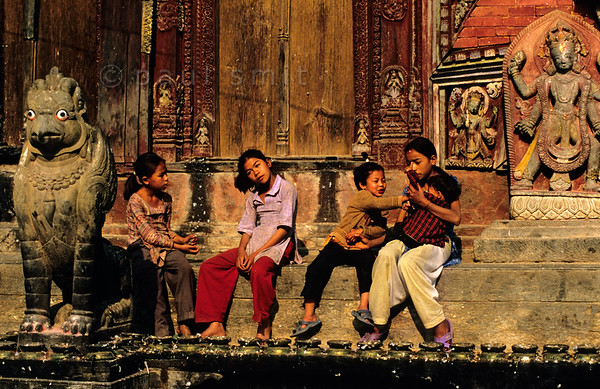 [NEPAL.KATHMANDUVALLEY 27549] 'Children at Changu Narayan.'  	Local children and a griffin are enjoying the morning sun at the eastern entrance of the Vishnu Temple (ca. 1700) at Changu Narayan (north of Bhaktapur). Photo Paul Smit.