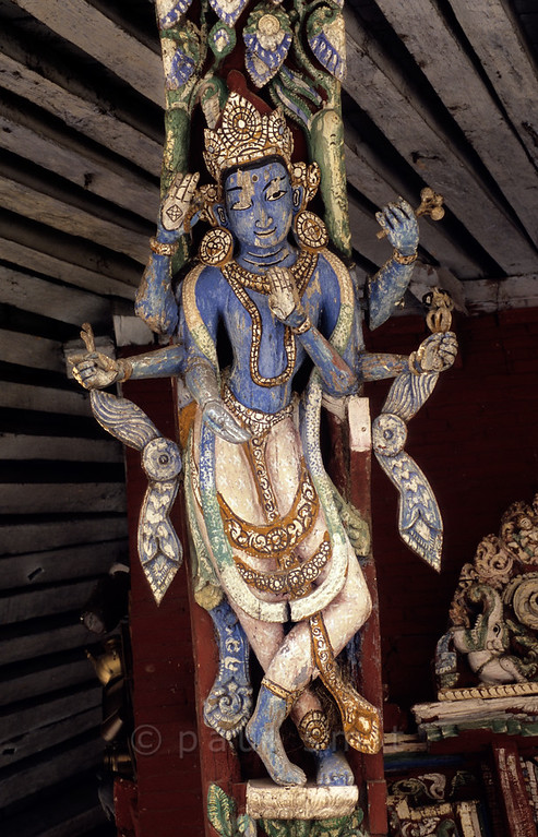 [NEPAL.KATHMANDUVALLEY 27341] 'Goddess of abundance.'  A roof strut of Patan's Rato Machhendranath Temple (1673) shows Vasundhara, the six armed goddess of abundance and consort of Kuvera, the Hindu god of wealth. In her upper left arm she holds her characteristic attribute, an ear of corn. Photo Paul Smit.