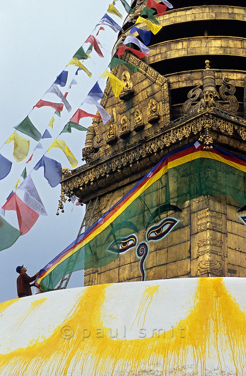 [NEPAL.KATHMANDUVALLEY 27214] 'Decorating Swayambhu stupa.'  	Watched over by the all-seeing eyes of Adi-Buddha (primordial Buddha) a temple guard is attending to the central stupa of Swayambhu, at the western outskirts of Kathmandu. The eyes are attached to the gold gilded cube (harmika) that surmounts the stupa. Photo Paul Smit.