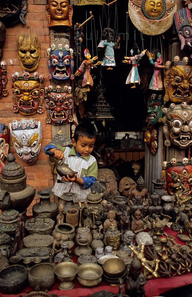 [NEPAL.KATHMANDUVALLEY 27228] 'Shop at Swayambhu.'  The little boy, son of the shop owner and playing with a bronze duck, is not at all impressed by the fierce looking masks behind him. They are the masks of Bhairava, the Hindu god of annihilation and the march of time. He is thought to preside over cremation grounds, hence the garland of skulls around his head. The matalware and mask shop can be found near the Swayambhu stupa, west of Kathmandu. Photo Paul Smit.