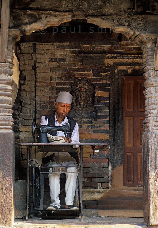 [NEPAL.KATHMANDUVALLEY 27388] 'Tailor in Bhaktapur.'  	A tailor is working in front of his house in Bhaktapur. Photo Paul Smit.