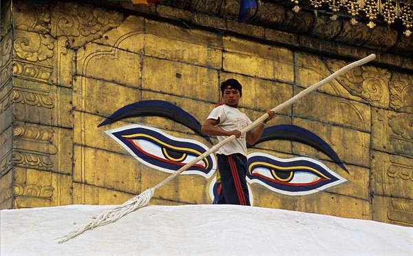 [NEPAL.KATHMANDUVALLEY 27199] 'Whitewashing Swayambhu stupa.'  	Watched over by the all-seeing eyes of Adi-Buddha (primordial Buddha) a boy is whitewashing the central stupa of Swayambhu, at the western outskirts of Kathmandu. The eyes are attached to the gold gilded cube (harmika) that surmounts the stupa. Photo Paul Smit.