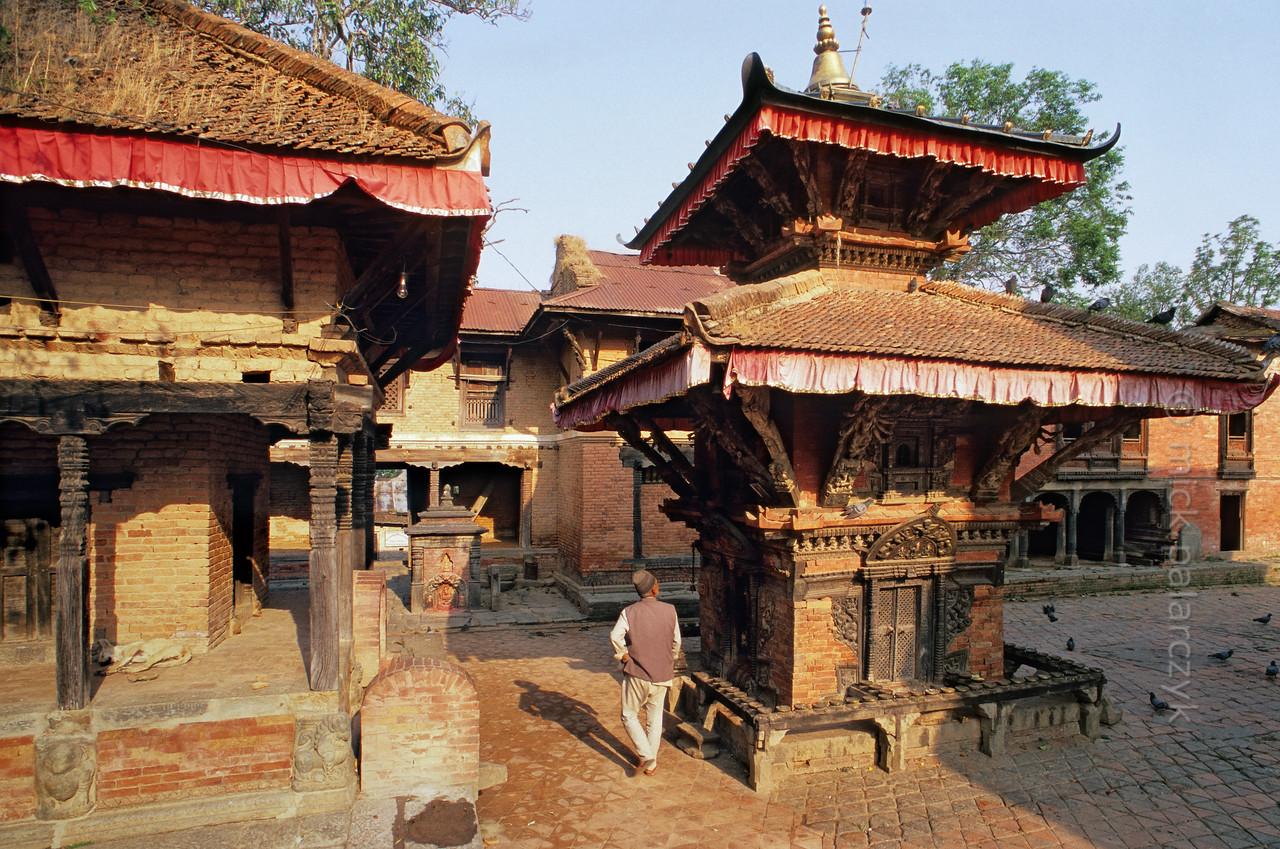 [NEPAL.KATHMANDUVALLEY 27548] 'Courtyard of Vishnu Temple in Changu Narayan.'  A man looks up at the roof struts of the Pashupatinath Shrine in the courtyard of the Vishnu Temple (ca. 1700) at Changu Narayan. Photo Mick Palarczyk.