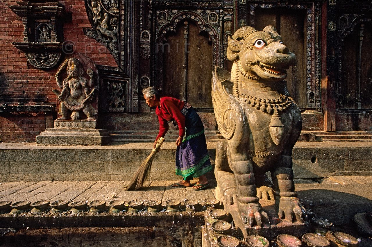 [NEPAL.KATHMANDUVALLEY 27535] 'Mythical monster at Changu Narayan.'  The northern entrance of the Vishnu Temple (ca. 1700) at Changu Narayan (north of Bhaktapur) is guarded by a mythical monster while its plinth is kept clean by a local old woman. Photo Paul Smit.